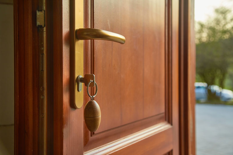 Home wooden door with key inserted in the lock