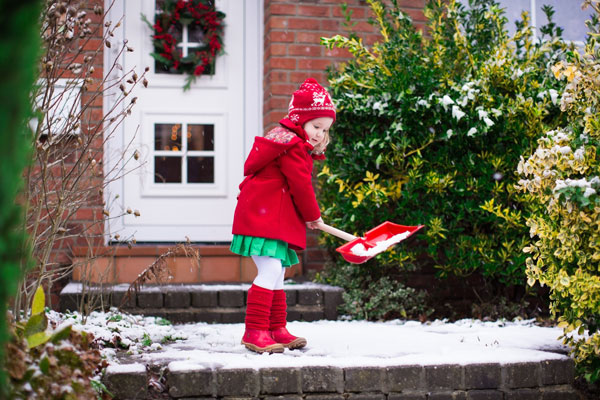 Young girl shoveling icy steps