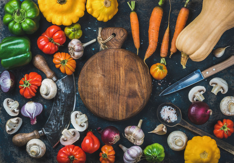 Cutting board with colorful vegetables to be sliced and diced