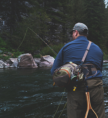 Fisherman with gear, backpack and pole
